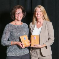 Deputy City Manager Kathleen Trepa (left) and Sustainability Coordinator Cindy Moore holding the City's two Beacon Spotlight Awards.